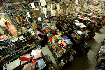 A customer checks checks a book at the 'Acapulco' bookstore in Ciudad Juarez