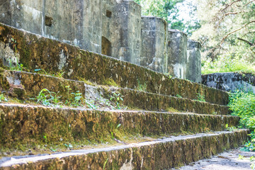 protective concrete mossy wall of ruined abandoned military fortress of the First World War in forest