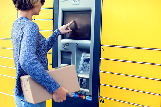 Woman using automated self service post terminal machine or locker to deposit the parcel for storage
