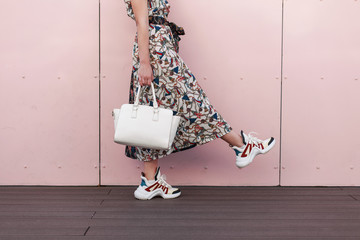 Stylish beautiful young woman in fashionable dress with stylish white bag and trendy sneakers is near the pink wall. The concept of shopping