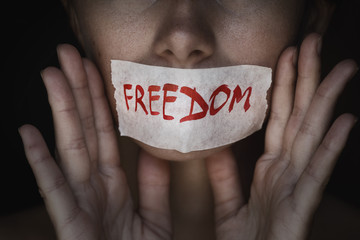 Concept of freedom speech: mouth of a person is sealed with an adhesive tape, closeup