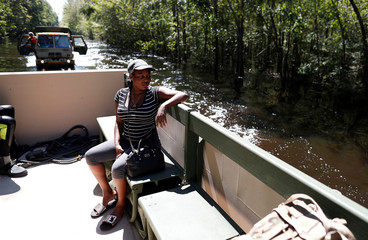 After being stranded for five days at her home, Jay Gerald checks the flood waters from a National Guard transport vehicle while being evacuated in the aftermath of Hurricane Florence in Whiteville