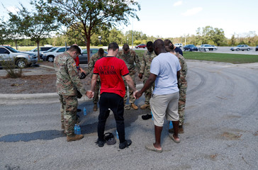 Members of the Quapaw Tribe Fire and Rescue Swift Team of Oklahoma and the 1st Combat Engineer Company of the U.S. National Guard of Laurinburg, NC, hold a prayer circle outside the Red Cross shelter after transporting flood victims