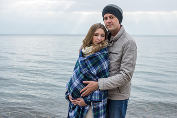 Husband wraps a blanket pregnant woman with a belly. Autumn nature by the sea. Concept of motherhood and care