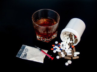 Pills of different sizes, shapes and colors, a glass of whiskey, drugs and syringes Concept of drugs and alcohol