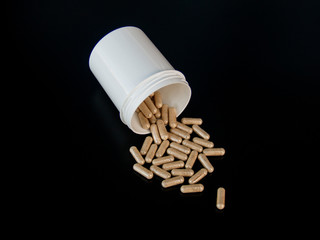 A pot of capsules with black background. Health concept