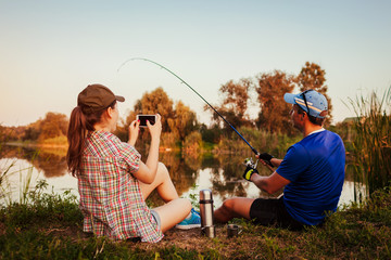 Young couple fishing and drinking tea on river at sunset. Woman filming her boyfriend catching fish. People having fun