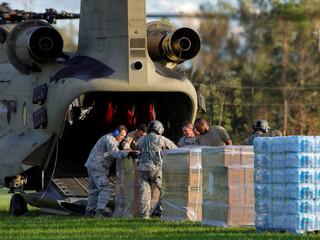 U.S. Army personnel unload food and water from a CH-47 Chinook helicopter they delivered to a community isolated by the effects of Hurricane Florence, now downgraded to a tropical depression, in Atkinson, North Carolina