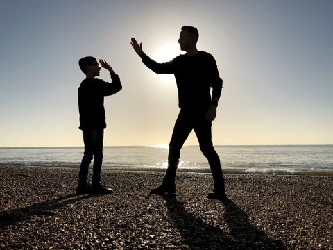 Silhouette of a Father and son standing on beach high fiving, Southsea, Hampshire, United Kingdom