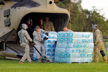 U.S. Army personnel unload food and water from a CH-47 Chinook helicopter delivering the needed supplies to a community isolated by the effects of Hurricane Florence, now downgraded to a tropical depression, in Atkinson, North Carolina