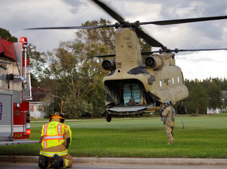 A local fireman crouches as a U.S. Army CH-47 Chinook helicopter maneuvers to readjust its payload as it delivers food and water a community isolated by the effects of Hurricane Florence, now downgraded to a tropical depression, in Atkinson, North Carolina