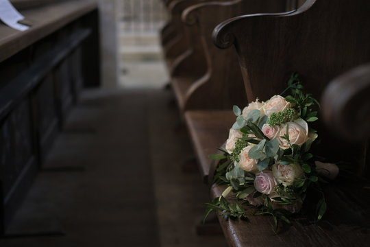 Bouquet of roses on a bench in a church