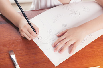 hand of school girl drawing picture with pencil, education concept.