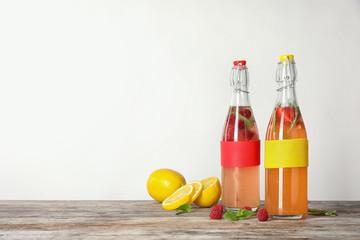 Bottles with natural lemonade on table against white background