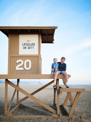 Two brothers sitting on a lifeguard tower, Orange County, California, United States