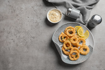Homemade crunchy fried onion rings and sauce on gray background, top view. Space for text