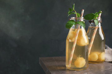Bottles with tasty melon ball drink on table against dark background. Space for text