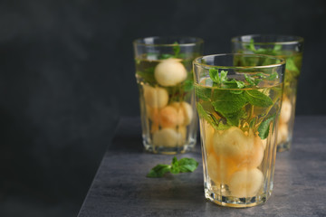 Glasses with tasty melon ball drink on table against dark background. Space for text