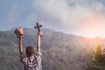 Boy holding holy Bible and christian cross with light sunset background. young christian concept
