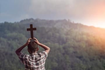 Boy raised the cross of christian overhead