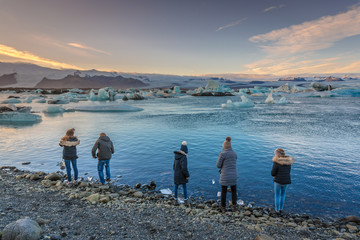 Tourists at the edge of the iceberg lagoon with sunset colors, cold weather, Iceland