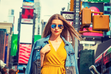 Young Eastern European Woman traveling in New York, with long brown hair, wearing yellow dress, blue Denim jacket draped over shoulder, blue sunglasses, standing on street in Times Square of Manhattan
