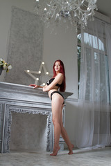 girl in lingerie is standing in a room with a fireplace