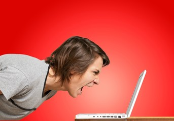 Furious young man screaming on laptop