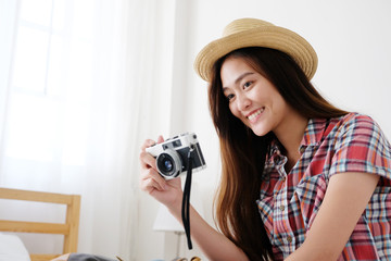 Young asian woman holding vintage camera with smiling while preparing to travel, people positive expression, travel summer holiday vacation concept