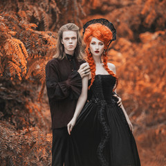Gothic couple in halloween costume. Gloomy vampire in victorian clothes. Redhead woman vampire in black victorian dress. Gothic clothes for halloween party. Gloomy couple on autumn background.