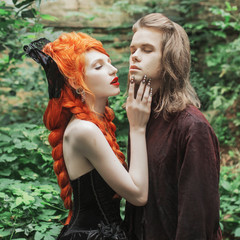 Gothic couple in halloween costume. Vampire in victorian clothes. Redhead woman dominant in black dress. Gothic clothes for halloween party. Couple on green summer background. Dominant in relations