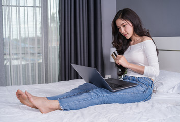 woman shopping online with credit card and laptop computer on bed