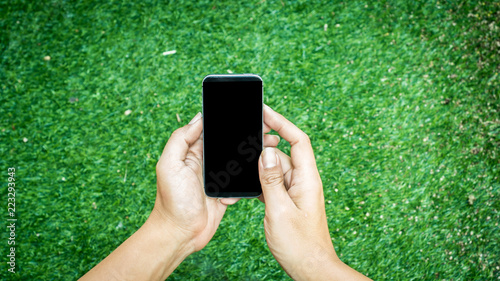 Wall mural Handsome man holding smart phone nature background
