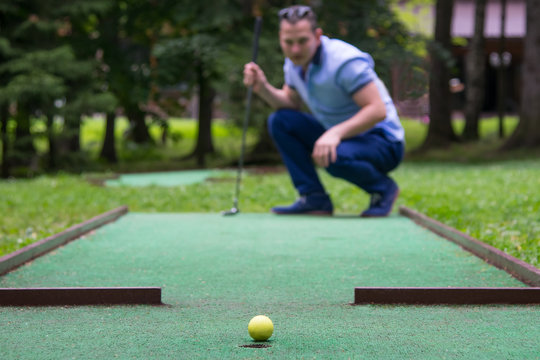 a mini-golf player looks at the result of a blow to the side of the pocket