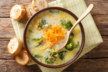 Delicious cheesy broccoli soup with vegetables in a bowl with toast close-up. horizontal top view