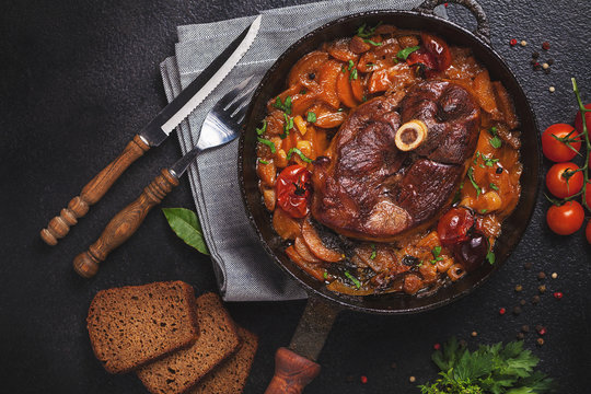 Ready-cooked meat on the bone Osso Buco in tomato sauce over black background of cast iron