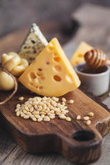 pine nuts on a wooden board and cheeses