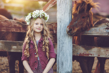 Cute little blonde girl with wreath of flowers playing  near horses ponies in the stables over...