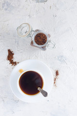 cup of coffee and  a glass jar with coffee powder