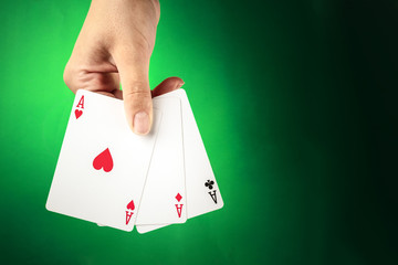 A hand holding three aces against a green background with copy space