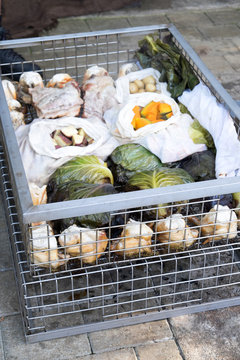 Hangi food: meat and vegetables cooked in a traditional Maori earth oven in a metal wire basket in New Zealand, NZ