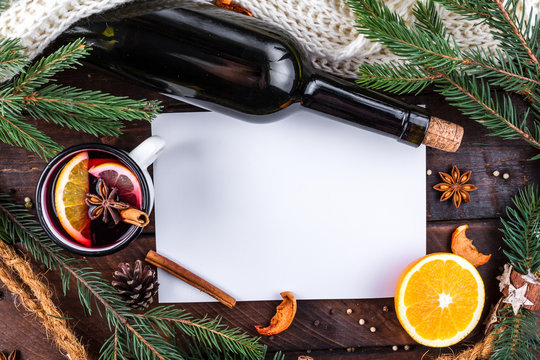 Mug of hot mulled wine with spices, citrus fruits, cinnamon and anise stars on a wooden background. Copy space. Top view. Flat lay. Mulled wine background. Winter drinks. Christmas, cozy evening