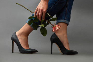 Elegant girl legs in jeans and high-heeled shoes, a girl's hand with a tattoo is holding a pink flower around a dark background with copy space.