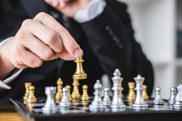 Hands of confident businessman playing chess game to development analysis new strategy plan, leader and teamwork concept for win and success