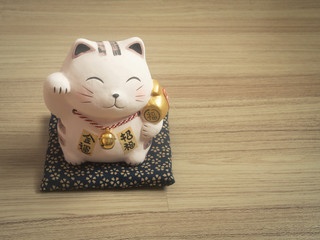 Lucky cat on wood background.