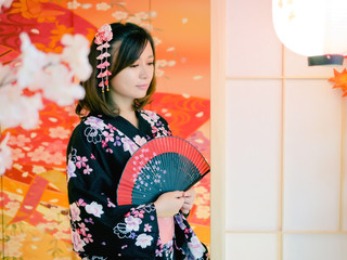 Portrait of attractive asian woman wearing traditional Japanese Kimono holding folding fan in hand, standing in front of sliding door, waiting someone coming home, lifestyle of authentic people.
