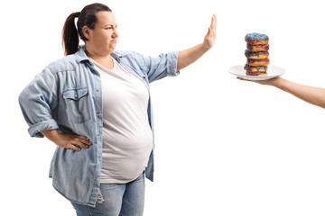 Overweight woman refusing to eat donuts