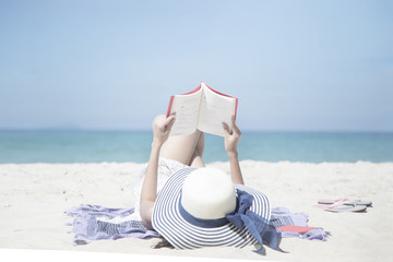 A portrait of beautiful asian woman holding red book in hand. Happy classic man on white sand at Andaman Sea with beautiful blue sky and clear water. Concept summer vacation holiday.