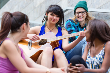 Ypung woman plying guitar with her diverse friends