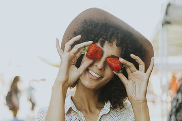 Woman having fun with strawberries